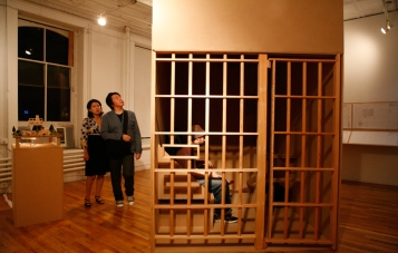 Observers view a model of Herman's cell at The House That Herman Built art exhibit.