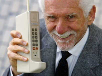 Martin Cooper, chairman and CEO of ArrayComm, holds a Motorola DynaTAC, a 1973 prototype of the first handheld cellular telephone, on April 2, 2003, in San Francisco. The device is 10 inches long and weighs 2.5 pounds.