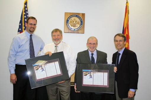 Jeff Schrade (left) and Justice Scott Bales (right) present framed Arizona Attorney articles to lawyer-authors Paul Julien (center-left) and Mark Maltzer, April 2013.