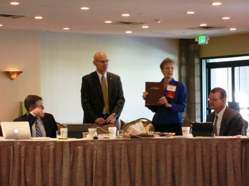 Amelia Craig Cramer opens her gift of a bound volume of Arizona Attorney Magazine, while State Bar CEO John Phelps looks on, June 18, 2013.