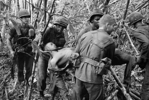 Soldiers of the 101st Airborne Division carried a wounded comrade through the jungle, May 1966. (AP, Henri Huet)