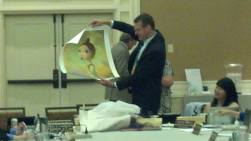 President Whitney Cunningham displays a gift of artwork.
