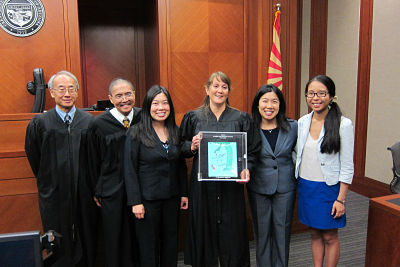 "AAABA members and past recipients Hon. Kenneth Lee and Hon. Paul Tang present AAABA's newest recipient, Hon. Joan L. Wagener, with ""The Book"" at her investiture ceremony on July 11, 2014 at the Arizona Superior Court in Pima County. Fellow members Briana Chua, Amanda Chua and Shijie Feng attended. (Photo: AAABA)"