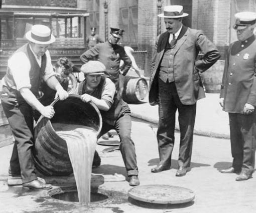 New York City Deputy Police Commissioner John A. Leach (at right in the jaunty straw hat) watches agents pour liquor into a sewer following a raid during the height of prohibition in an undated photo held by the Library of Congress. (REUTERS)