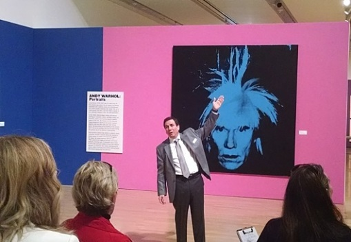 Curator Dr. Jerry Smith in front of a self-portrait of Andy Warhol.