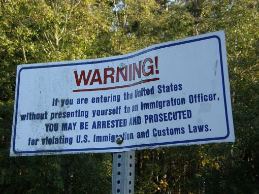 Warning sign posted at the international boundary between the United States and Canada in Point Roberts, Washington. (photo via Wikimedia Commons.)