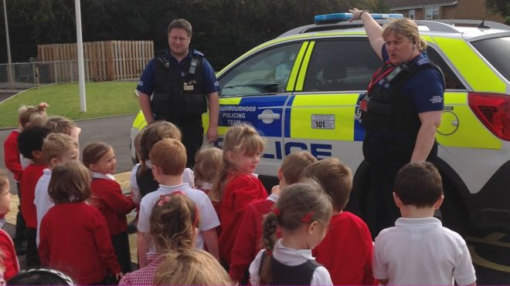 Police demonstrate their car and its multiple siren sounds to British schoolkids.