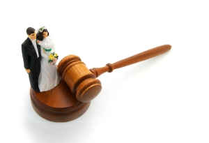 Plastic bride and groom with gavel, on white - divorce concept
