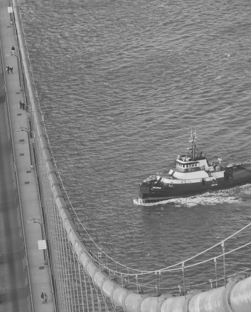 Tugboat passes beneath the Golden Gate Bridge, by Steve Mnich.